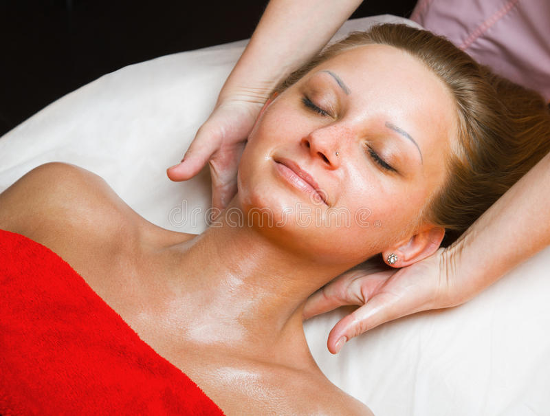 Beautiful woman receiving a massage. Beautiful woman receiving a neck massage royalty free stock images