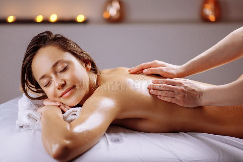 Spa body massage treatment. Woman having massage in spa salon royalty free stock images
