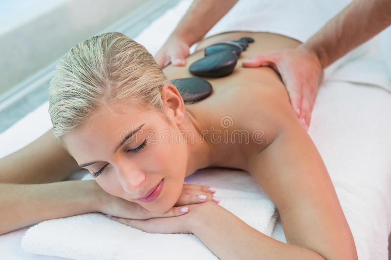 Beautiful woman receiving stone massage at health farm. Close-up of a beautiful young woman receiving stone massage at health farm stock photography