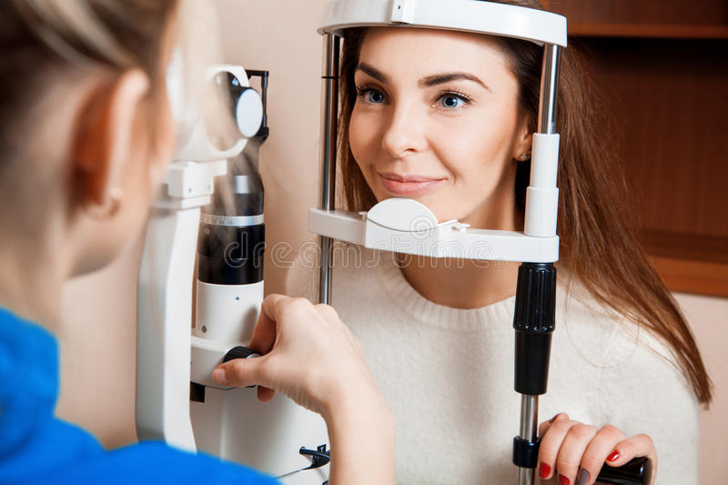 Beautiful woman on reception at the ophthalmologist checks her v. Beautiful women on reception at the ophthalmologist checks her vision. Ophthalmologist. medical stock images