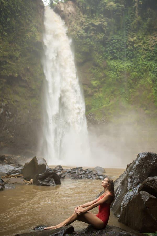Beautiful woman in red bikini and waterfall. stock image