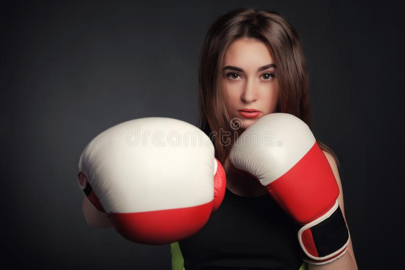 Beautiful woman with the red boxing gloves,black background stock photography