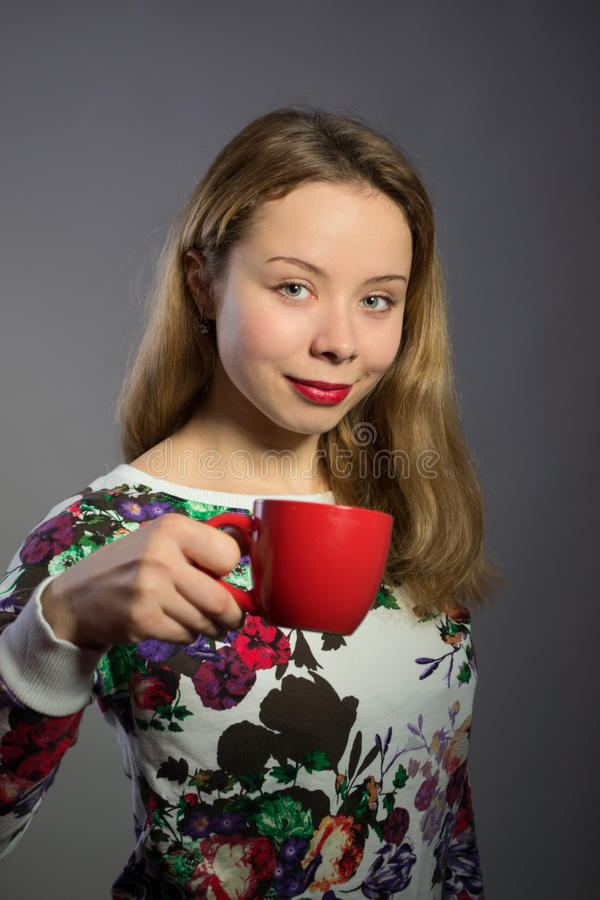 Beautiful woman with red cup of tea or coffee royalty free stock photos