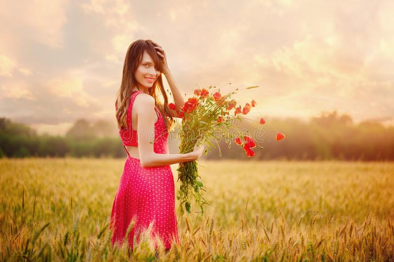 Beautiful woman in a red dress with a bouquet of poppies in a wheat field at sunset, warm toning, happiness and a healthy lifestyl royalty free stock images