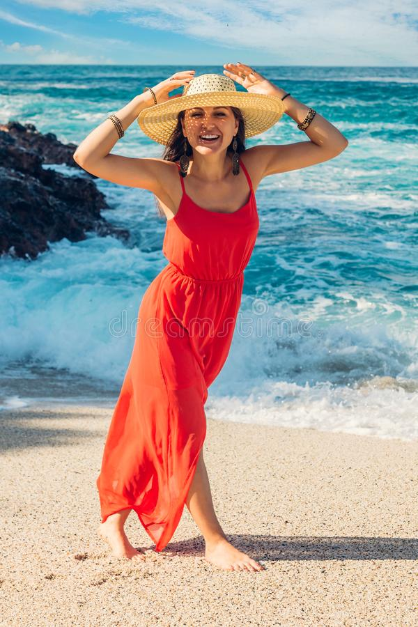 Beautiful woman enjoys the view of waves on sunny beach. Happy woman smiling. Summer vacation concept royalty free stock photo
