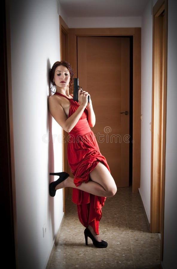 Beautiful Woman with a red dress and a gun. Portrait of Beautiful Young Woman With a red dress and a gun in a hallway stock photo