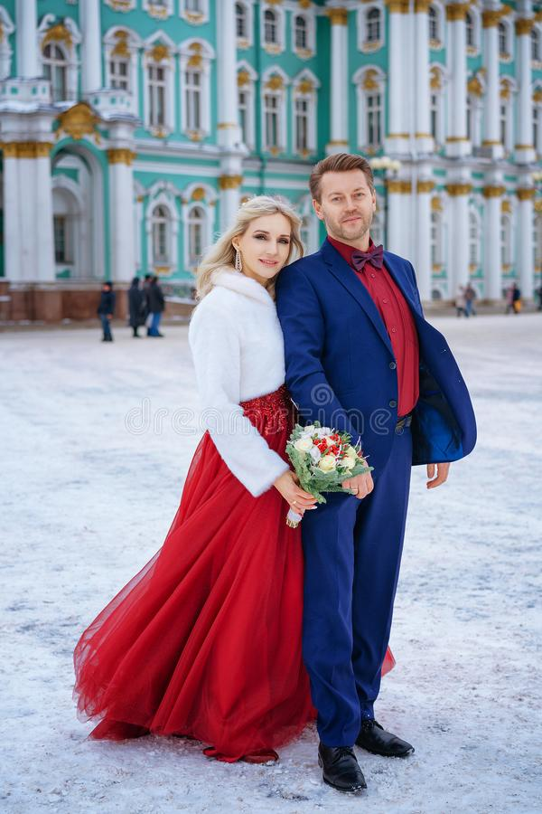 Beautiful woman in red dress and man posing standing in winter, wedding in St. Petersburg royalty free stock image