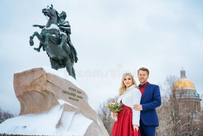 Beautiful woman in red dress and man posing standing in winter, wedding in St. Petersburg royalty free stock photography