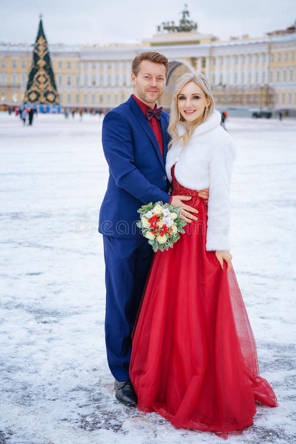 Beautiful woman in red dress and man posing standing in winter, wedding in St. Petersburg stock photography