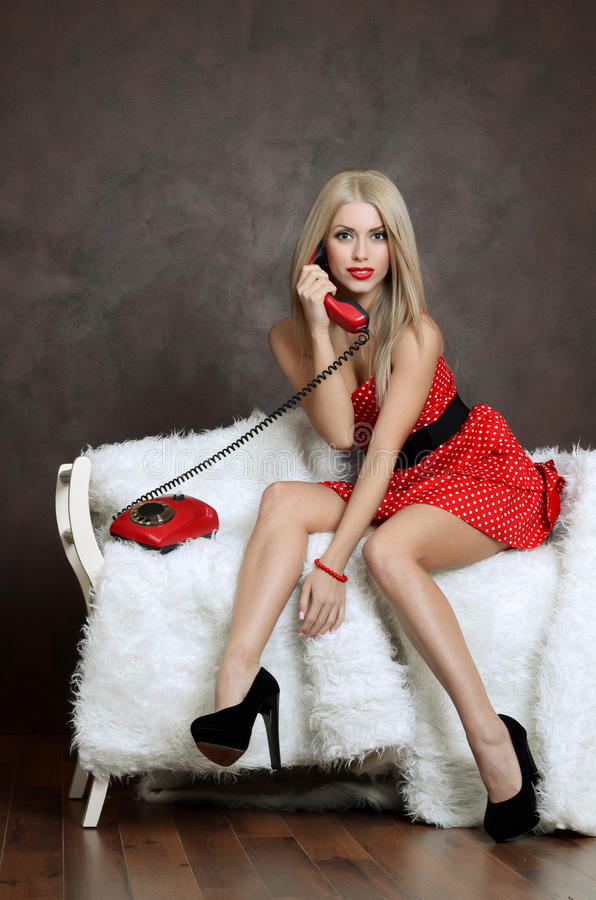 The beautiful woman in a red dress with old phone stock photo