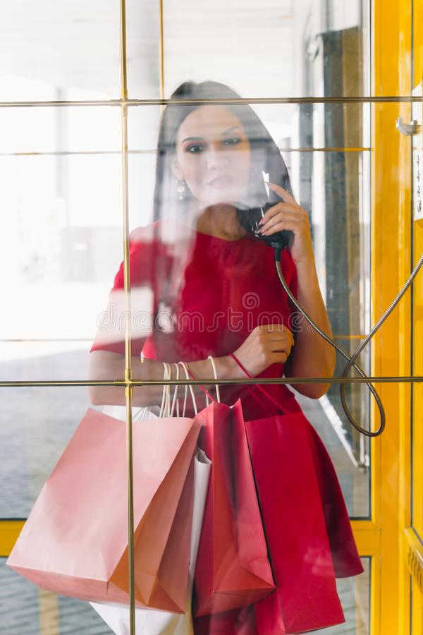 Beautiful woman in red dress orders a taxi in a retro phone booth in the mall after shopping. Young beautiful woman in red dress orders a taxi in a retro phone stock photo