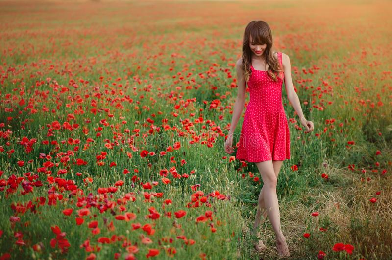 Beautiful woman in a red dress in a poppy field at sunset walking walks forward, warm toning, happiness and a healthy lifestyle stock images