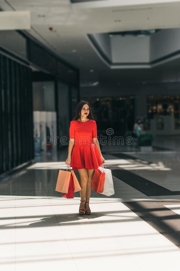 Young beautiful woman in red dress with shopping bags walking around the mall stock image