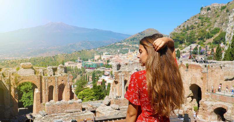 Beautiful woman with red dress in Taormina Greek theater with Etna volcano on the background in Sicily, Italy. Amazing panoramic stock photos
