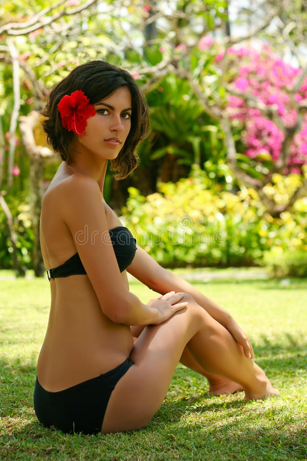 Beautiful woman with red flower relaxing in Bali. Hotel stock image
