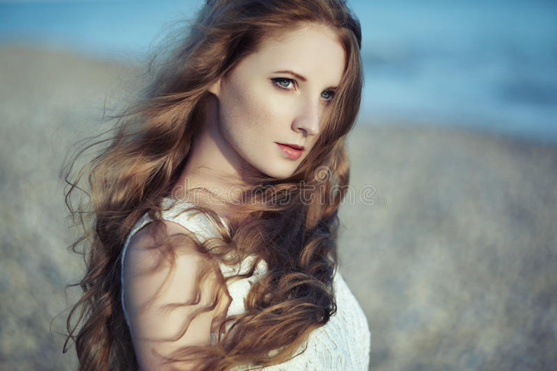 Beautiful woman with red hair at the sea. Fashiob photo stock photo