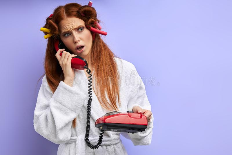 Young caucasian confused redhaired girl while talking on landline phone royalty free stock image