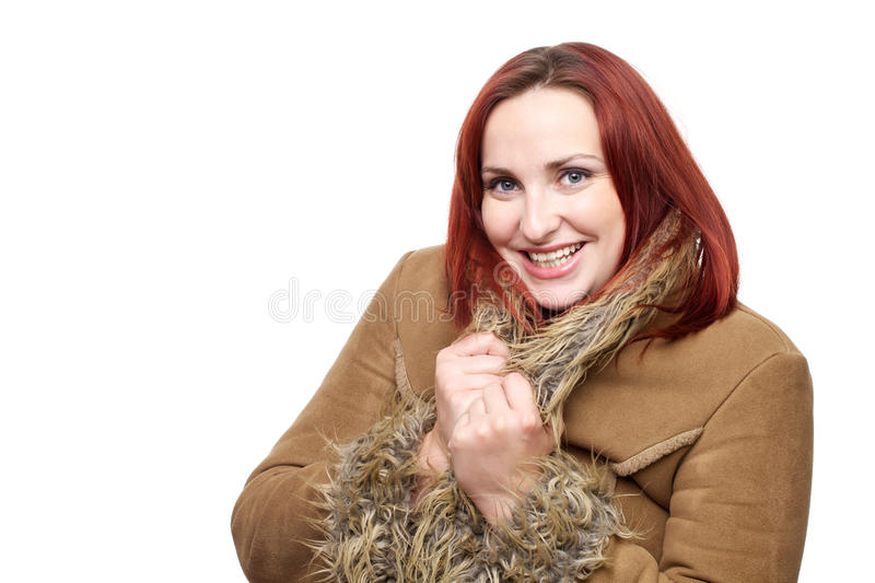 Beautiful woman with red hair in winter coat. Pretty young woman smiling and wearing a big winter coat with faux fur trim royalty free stock photos