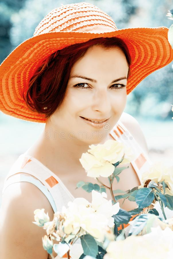 Beautiful woman in a red hat posing in garden royalty free stock photo