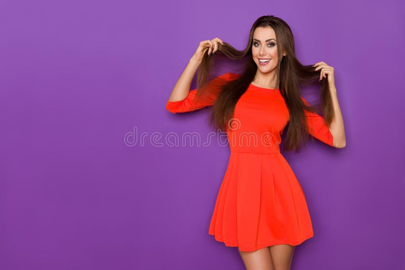Beautiful Woman In Red Mini Dress Is Holding Her Hair And Smiling stock image