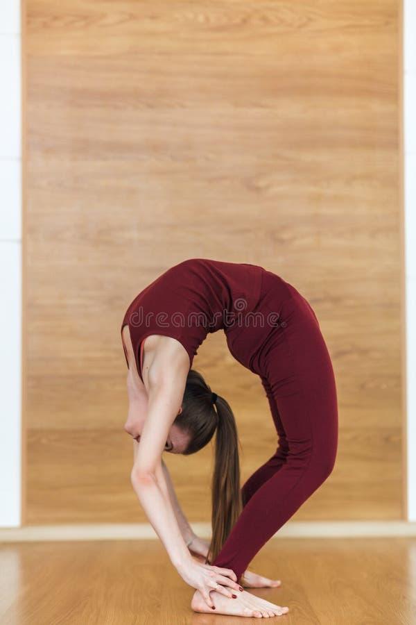Beautiful woman in red sportswear practices backbend yoga asana Urdhva Dhanurasana - Upward facing bow pose at the yoga studio. Beautiful woman in red stock images