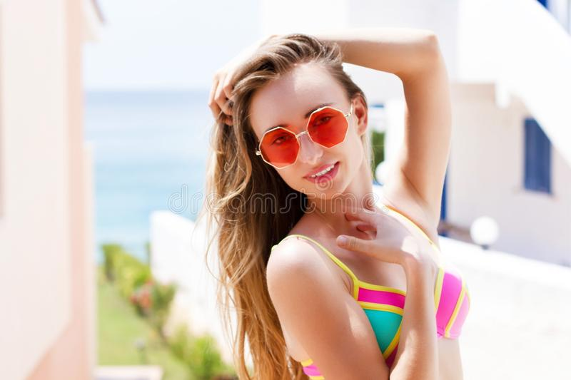 Beautiful woman in red sunglasses posing outdoor in summer on tropic island in hot weather in bikini fashion photo of beautiful stock image
