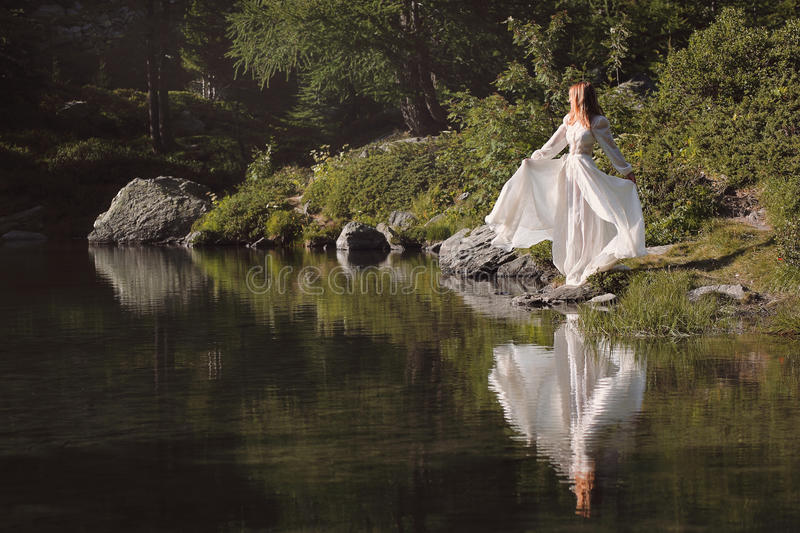 Beautiful woman reflected in alpine lake. Romantic and ethereal royalty free stock photo
