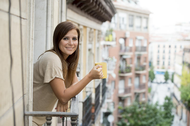 Beautiful woman relaxed cheerful drinking tea coffee at apartment balcony terrace stock image
