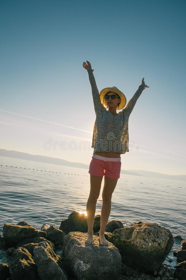 Beautiful woman relaxing on beach. Azure blue sea. Summer vacation. Straw hat. Young girl enjoys summer holiday. royalty free stock photography