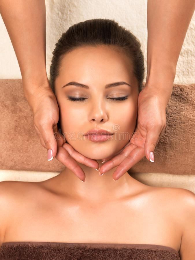 Beautiful woman relaxing and getting head massage. Portrait of beautiful young healthy woman relaxing and getting head massage in the spa salon royalty free stock photography