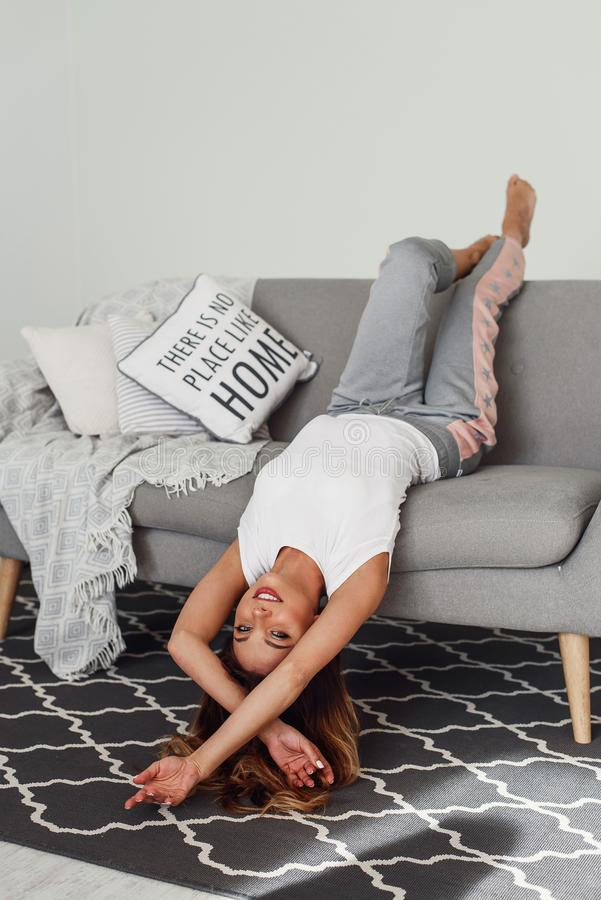 Beautiful woman relaxing on a grey couch with head upside down. Cute girl having fun at cozy home in lazy day. A beautiful woman relaxing on a grey couch with stock photo
