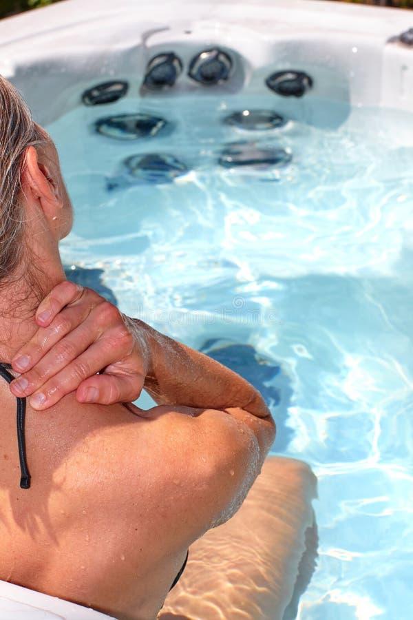 Beautiful woman relaxing in hot tub. Young beautiful woman relaxing in a hot tub stock images