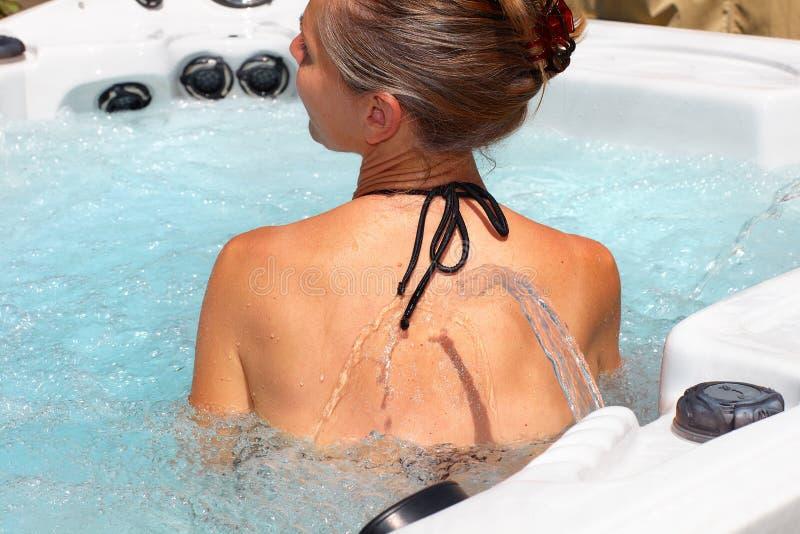 Beautiful woman relaxing in hot tub. Young beautiful woman relaxing in a hot tub royalty free stock image
