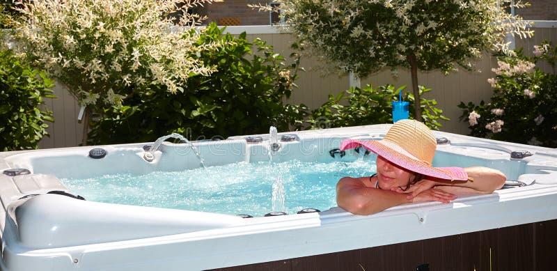 Beautiful woman relaxing in hot tub. stock photos