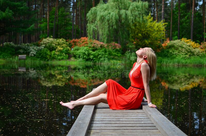 Beautiful woman relaxing by lake royalty free stock images