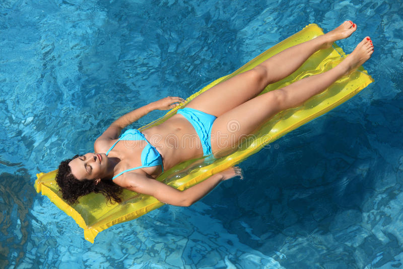 Beautiful woman relaxing on an mattress in pool royalty free stock image