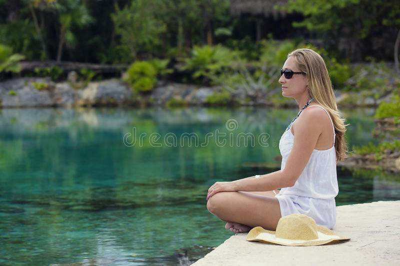 Beautiful woman relaxing and meditating in a jungle pool royalty free stock photo