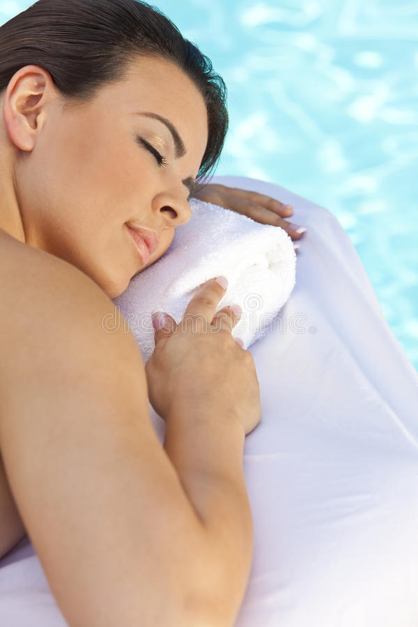 Beautiful Woman Relaxing By Pool At Health Spa royalty free stock photography
