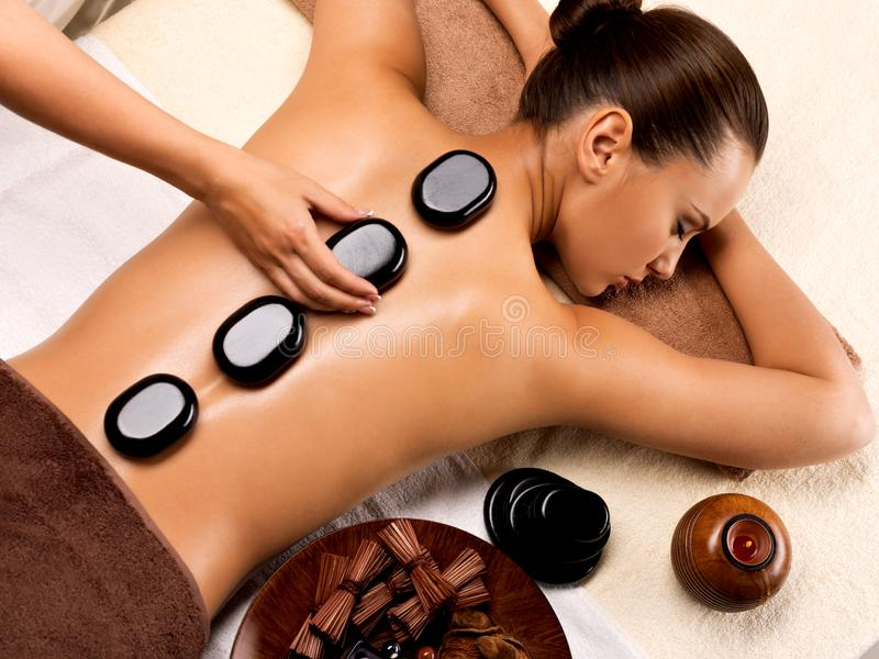 Beautiful woman relaxing in spa salon with hot stones on body. Beauty treatment therapy royalty free stock photos