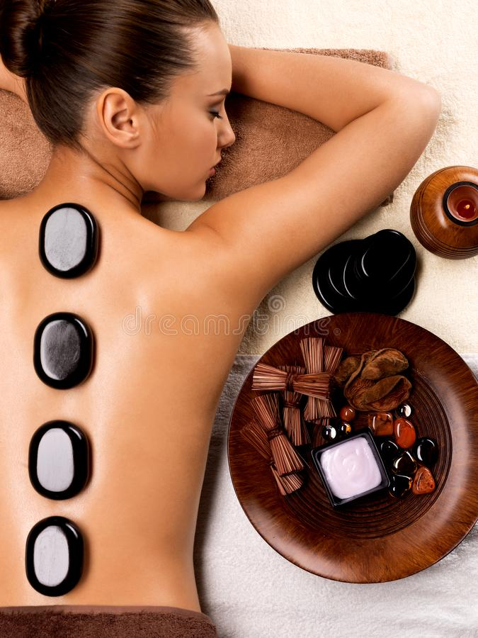 Beautiful woman relaxing in spa salon with hot stones on body. Beauty treatment therapy royalty free stock images