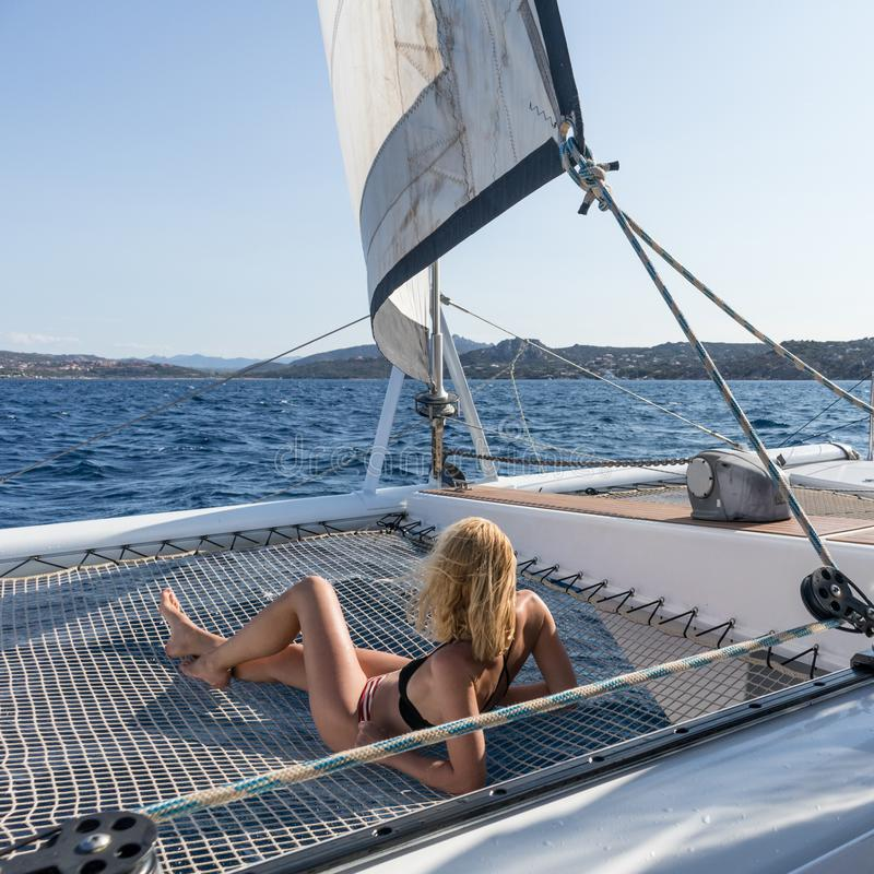 Beautiful woman relaxing on a summer sailing cruise, lying and sunbathing in hammock of luxury catamaran sailing around. Maddalena Archipelago, Sardinia, Italy stock images