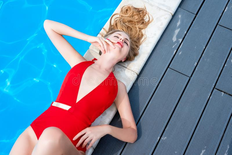 Beautiful woman relaxing in swimming pool. Blonde girl with gorgeous face, fashion makeup and wet hair enjoying summer sun on. Hot summer day at pool at luxury royalty free stock photos