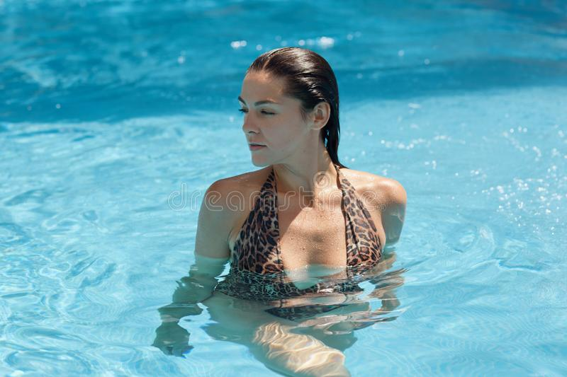 Beautiful woman relaxing in swimming pool in blue clear water. Girl with healthy tanned skin posing in swimming pool, looking stock images