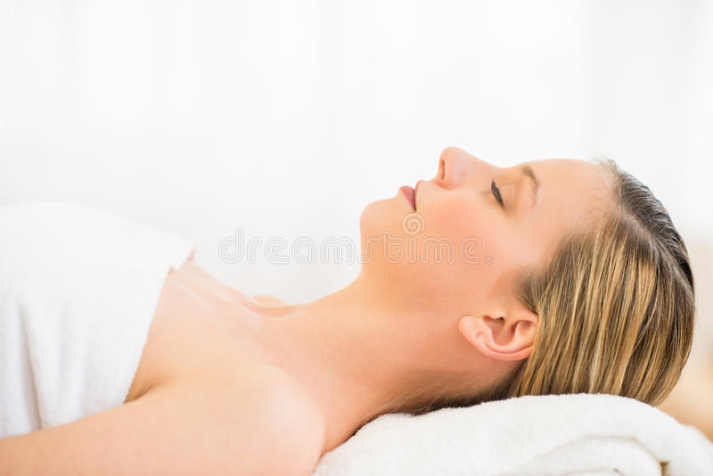 Beautiful Woman Resting On Massage Table In Health Spa. Side view close-up of beautiful young woman resting on massage table in health spa royalty free stock images