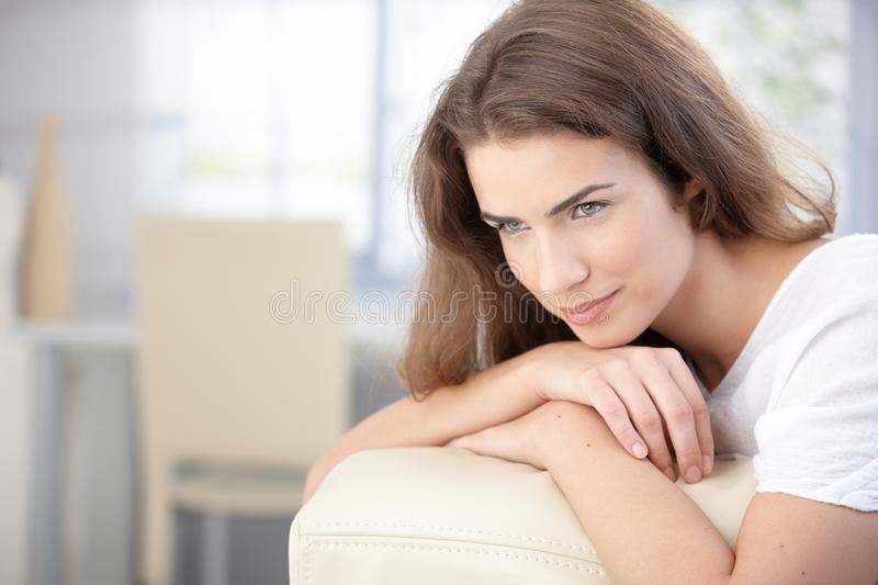 Beautiful woman resting on sofa smiling royalty free stock photography
