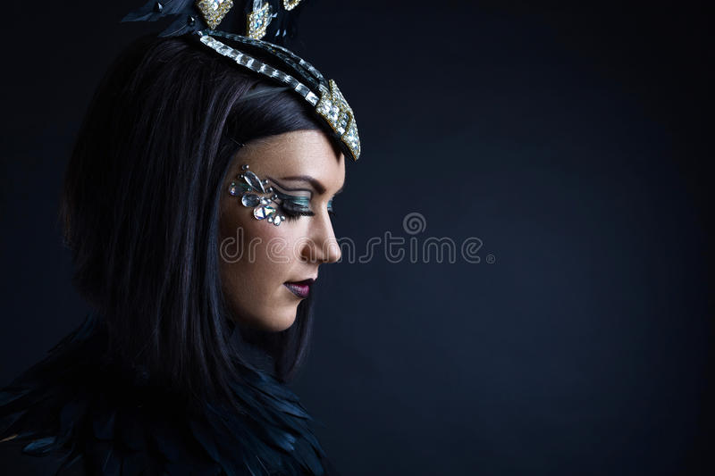 Beautiful woman in retro style with ornaments of rhinestone. Portrait of young beautiful woman in black with ornaments of rhinestone and feathers stock photos