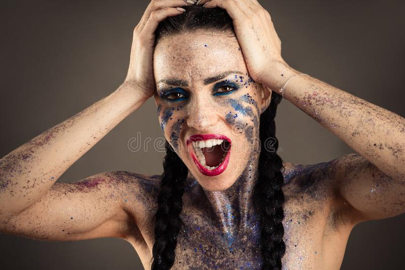 Beautiful woman with rhinestones cries holding head royalty free stock photo