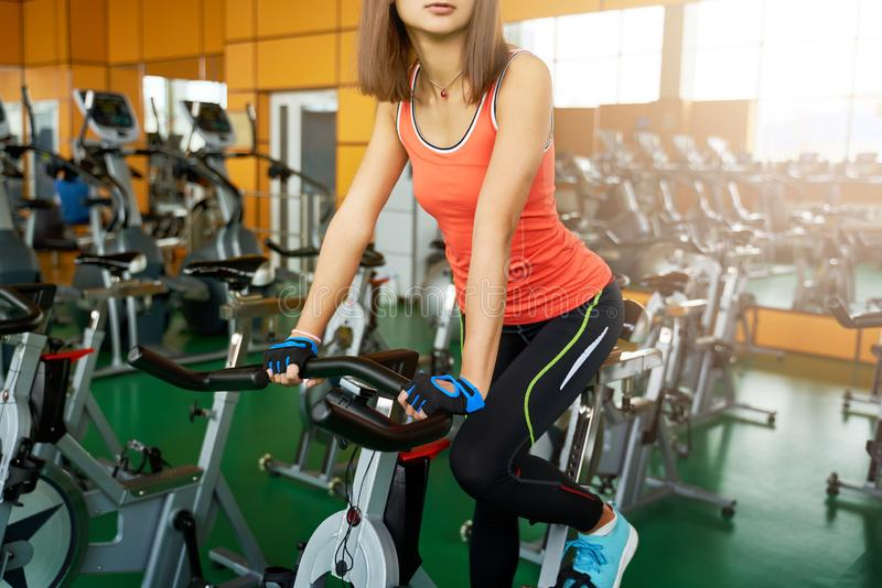 Beautiful woman riding a bike in the gym. Silhouette of a young girl doing sports stock image