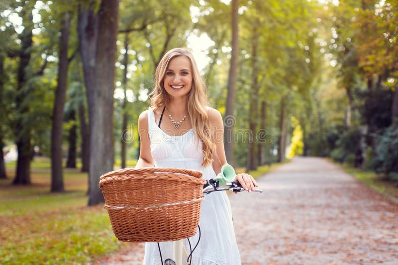 Beautiful woman riding her bicycle in a park royalty free stock photos