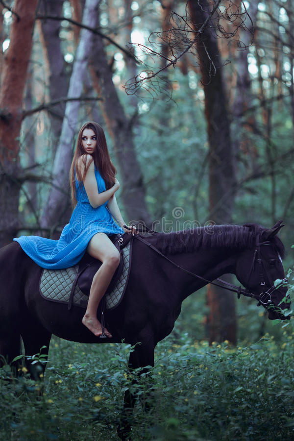 Beautiful woman riding horse in forest stock images